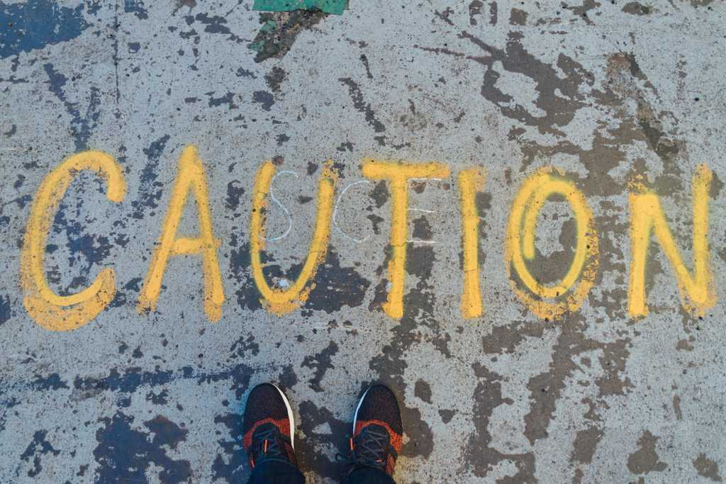 Caution written in chalk on a pavement with a person in running shoes standing in front