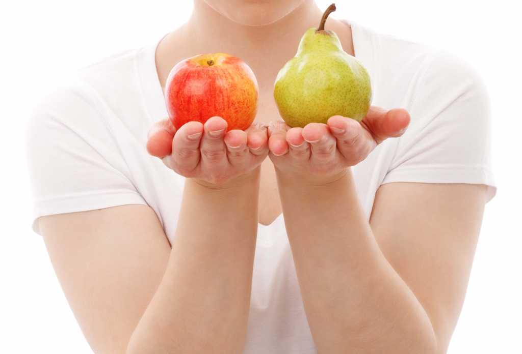 woman holds an apple in one hand and pear in the other in front of her body with white background