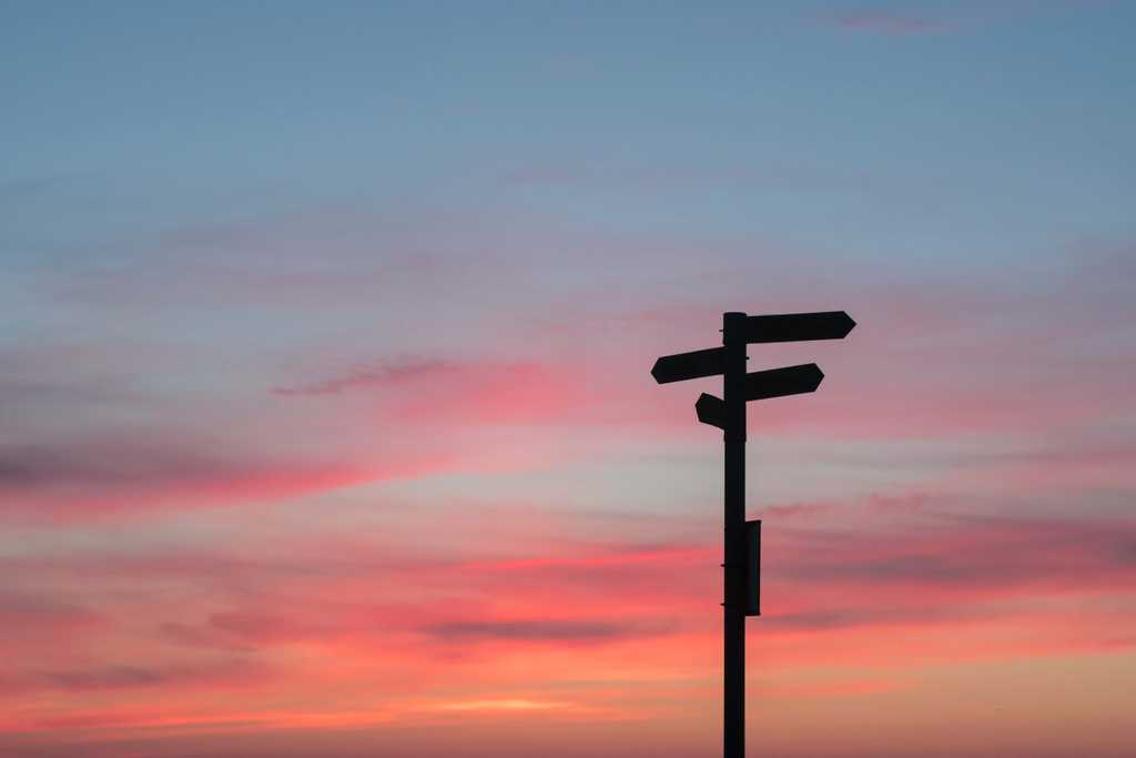 wooden sign points in multiple directions in front of pink sky during sunset