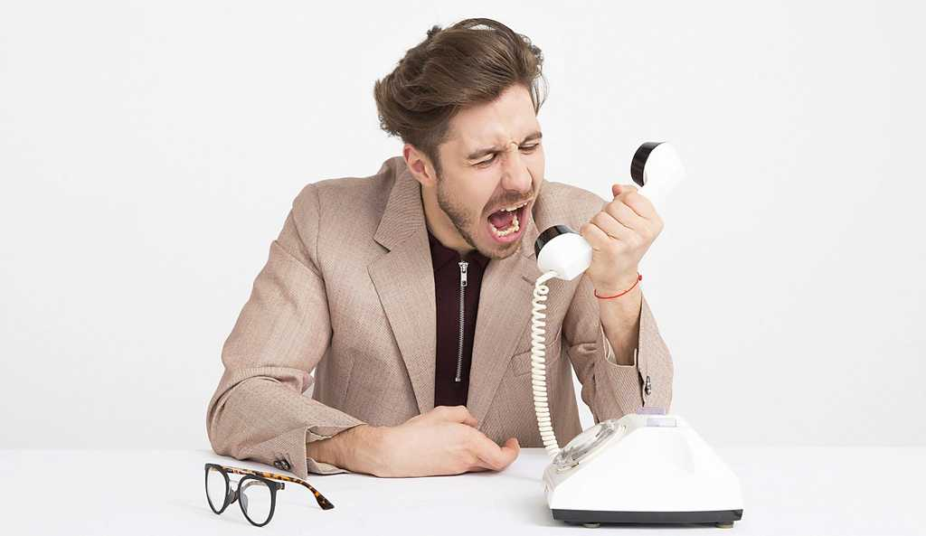 man screams in white telephone angrily with his eye glasses sitting on the table